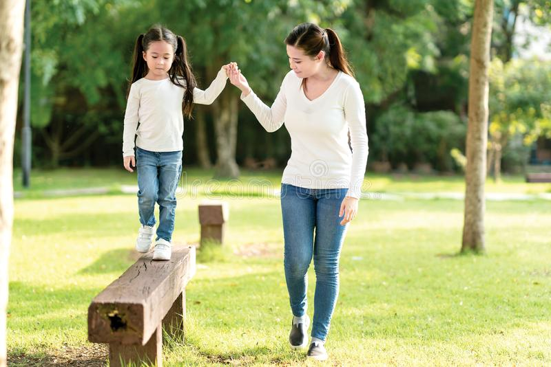 Asian mom and cute baby kid holding hand playing together at wood log walk in nature park outdoor playground in casual white blue royalty free stock photography