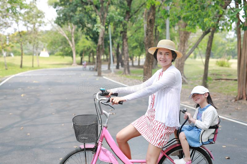 Asian mom and daughter riding bicycle together in park. Happy family stock photo