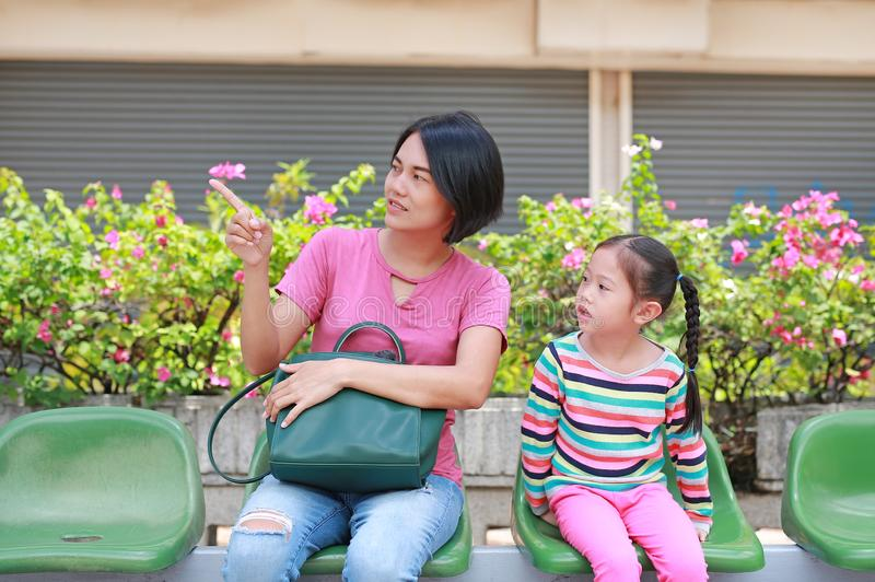 Asian mom and her daughter sitting on public transport bus. Mom pointing something to child girl looking stock photography