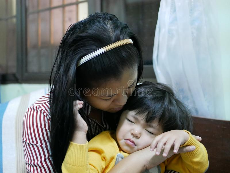 Asian mom with her little sleeping baby girl in her hands royalty free stock photography