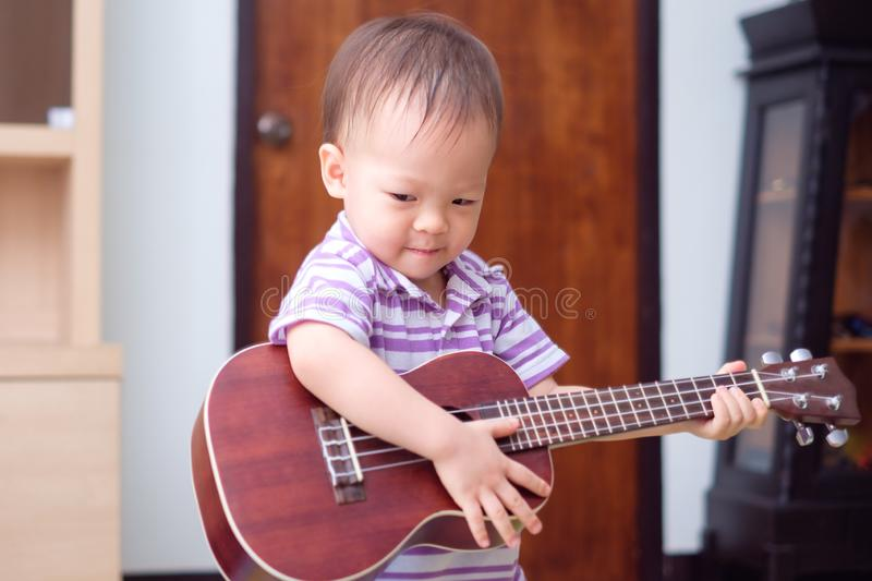 Asian 18 months / 1 year old baby boy child hold & play Hawaiian guitar or ukulele royalty free stock photos