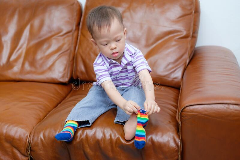 Asian 18 months / 1 year old toddler boy child sitting on sofa in living room concentrate on putting on his own socks. Cute little Asian 18 months / 1 year old royalty free stock images