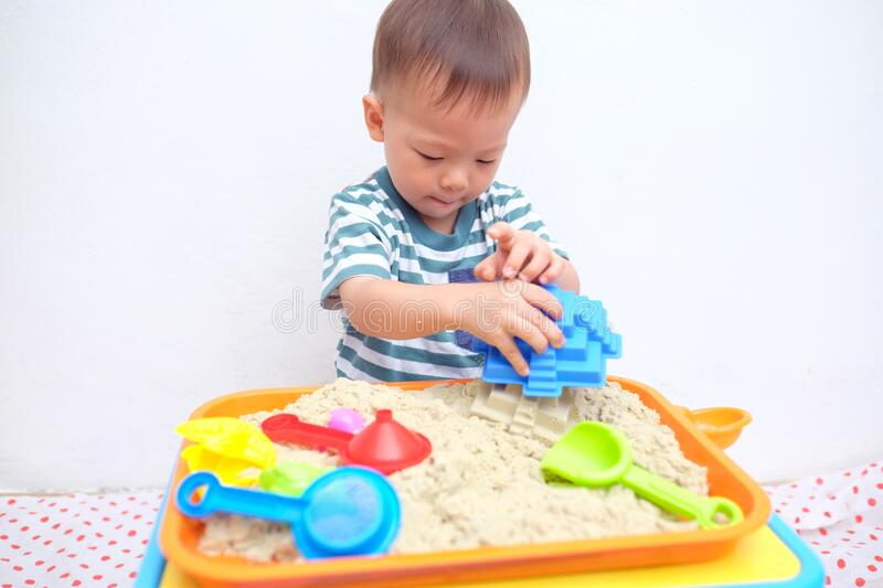 Asian 18 months / 1 year old toddler boy playing with kinetic sand at home ,Fine motor skills development. Cute little Asian 18 months / 1 year old toddler boy stock images