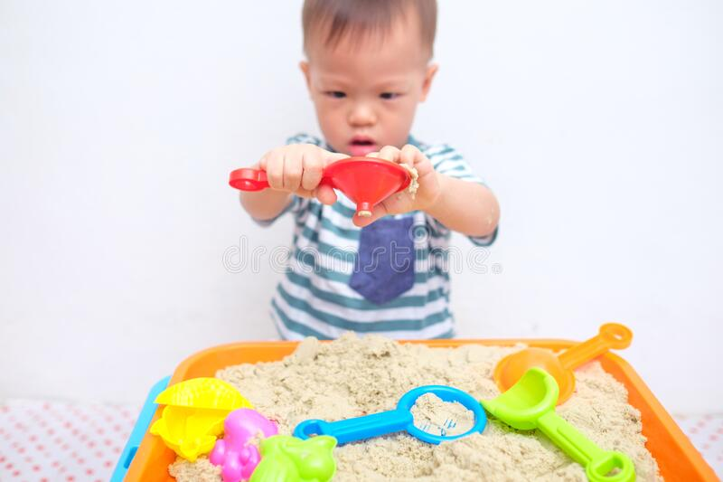 Asian 18 months / 1 year old toddler boy playing with kinetic sand at home ,Fine motor skills development, Montessori education,. Cute little Asian 18 months / 1 royalty free stock image
