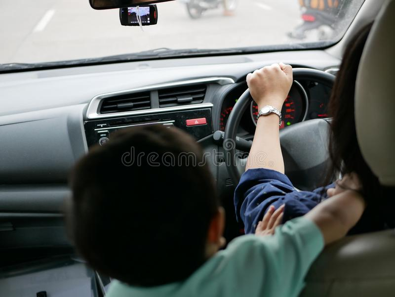 Asian mother being disturbed by her daughter, while she is driving a car royalty free stock photography