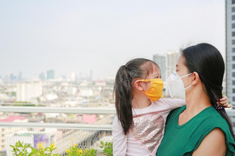 Asian mother carrying her daughter with wearing a protection mask against PM 2.5 air pollution in Bangkok city. Thailand stock photography