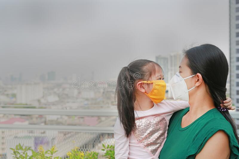 Asian mother carrying her daughter with wearing a protection mask against PM 2.5 air pollution in Bangkok city. Thailand royalty free stock images