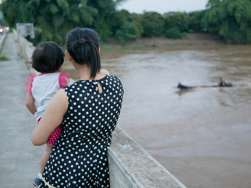 Asian mother carrying her little baby girl standing on a bridge watching a long-tail boat passing by on the river royalty free stock images