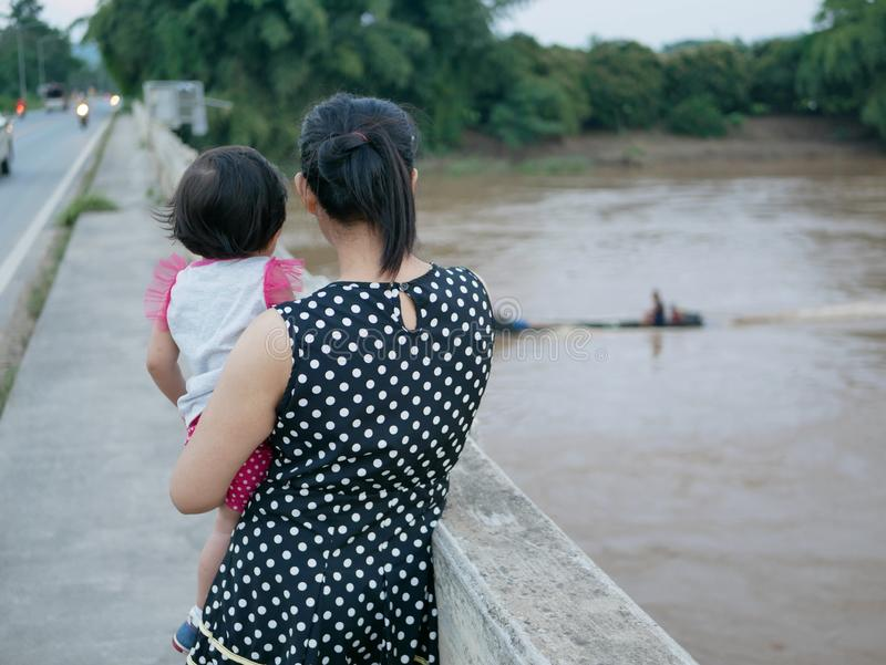 Asian mother carrying her little baby girl standing on a bridge watching a long-tail boat passing by on the river. Asian mother carrying her little baby girl stock images