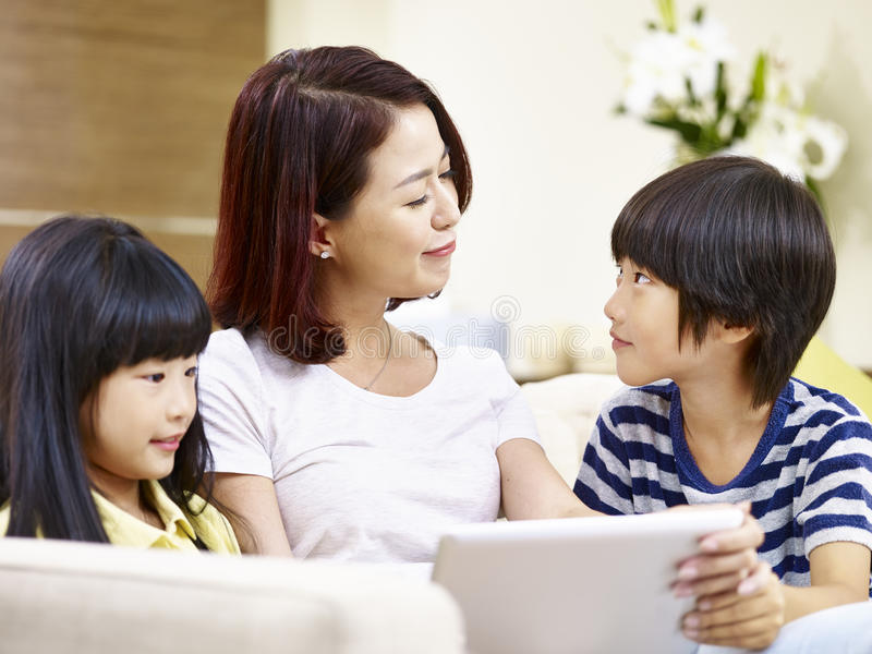Asian mother and children having fun at home stock photos