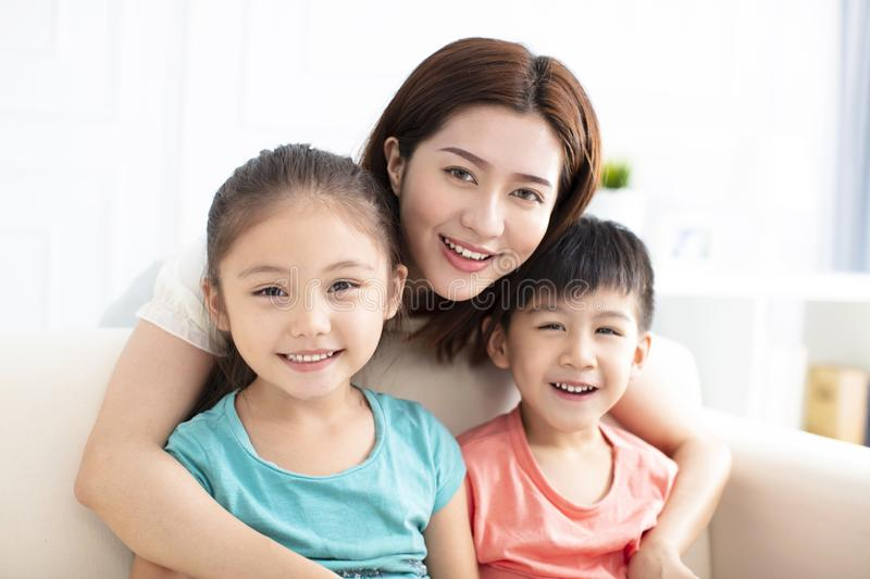 Mother and children smiling on couch royalty free stock photography
