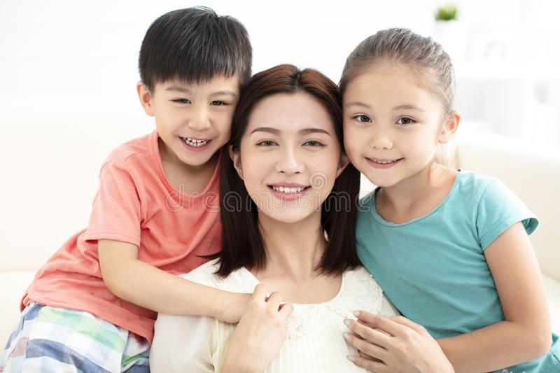 Mother and children smiling on couch royalty free stock image