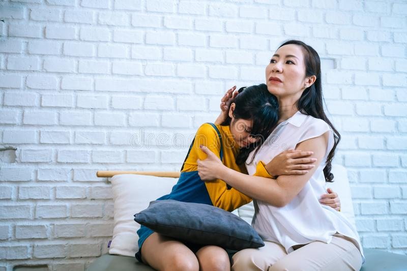 Asian mother comforting crying teenage daughter in miserable, stressed, depressed, sad state of mind. 40s Mom is hugging this adolescent teenager shoulders at stock photography