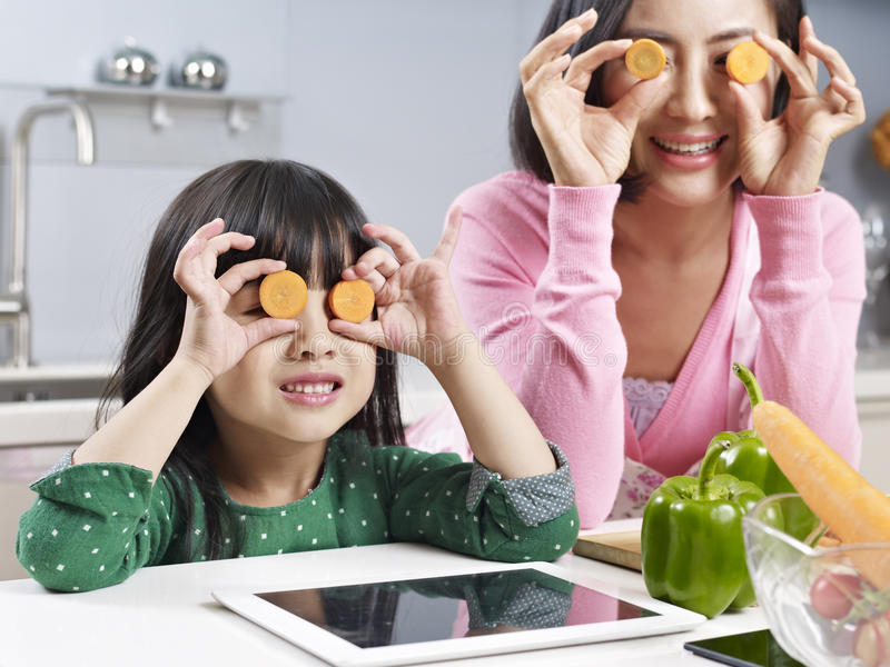 Asian mother and daughter in kitchen stock photography