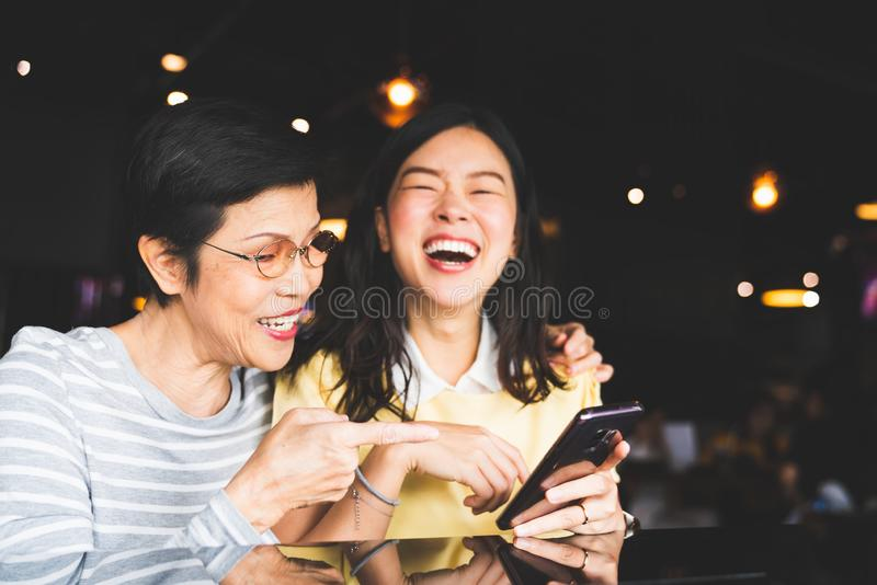 Asian mother and daughter laughing and smiling on a selfie or photo album, using smartphone together at restaurant or cafe stock photography