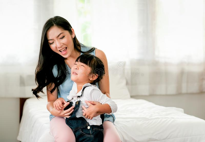 Asian mother and daughter play together in bedroom with mother sit on bed and they look fun and happy.  royalty free stock photos
