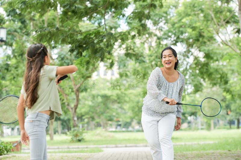 Asian mother and daughter playing badminton stock photo