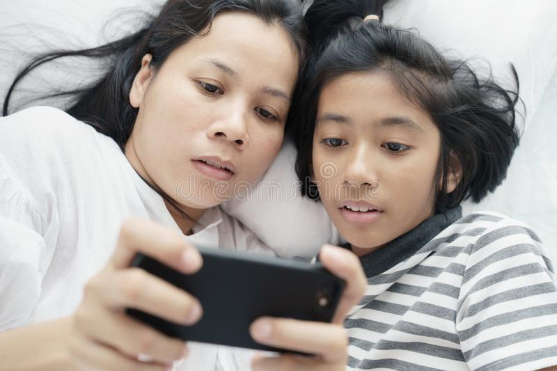 Asian mother and daughter playing game with phone together on the bed. Women and girl so happy and fun in bedroom royalty free stock images