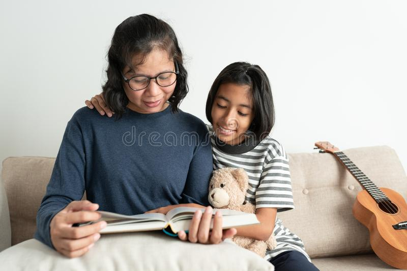 Asian mother and daughter read a book while sitting on the sofa. The little girl smiled and hugged his doll in the living room at royalty free stock photo