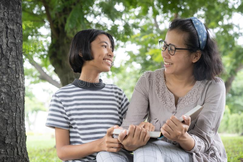 Asian mother and daughter reading book in the garden stock images