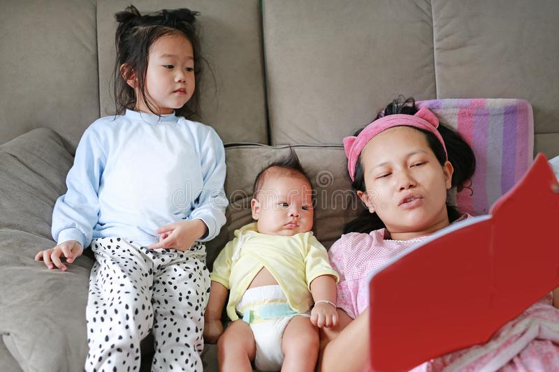Asian mother with daughter and son read fairy tale. Female with her little children enjoying book indoors stock photography