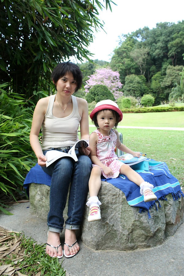 Asian mother and daugther reading at garden stock photos