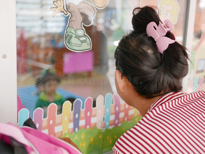 Asian mother eagerly looking at her baby through a window at a nursery school. Asian mother eagerly looking at her baby through a window while come to fetch her royalty free stock images