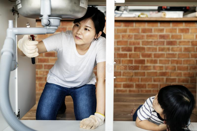 Asian mother fixing kitchen sink royalty free stock photo