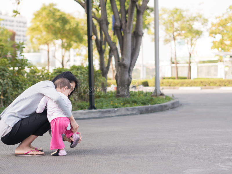 Asian mother help toddler wearing shoes. royalty free stock images
