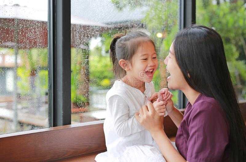 Asian mother and her daughter playing with love near a window while raining day stock images