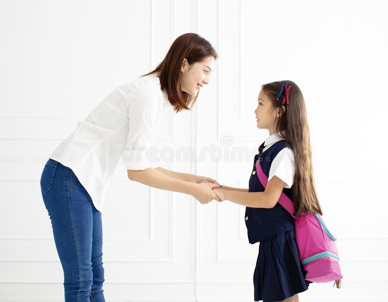 Mother holding hand of daughter ready go to school stock images