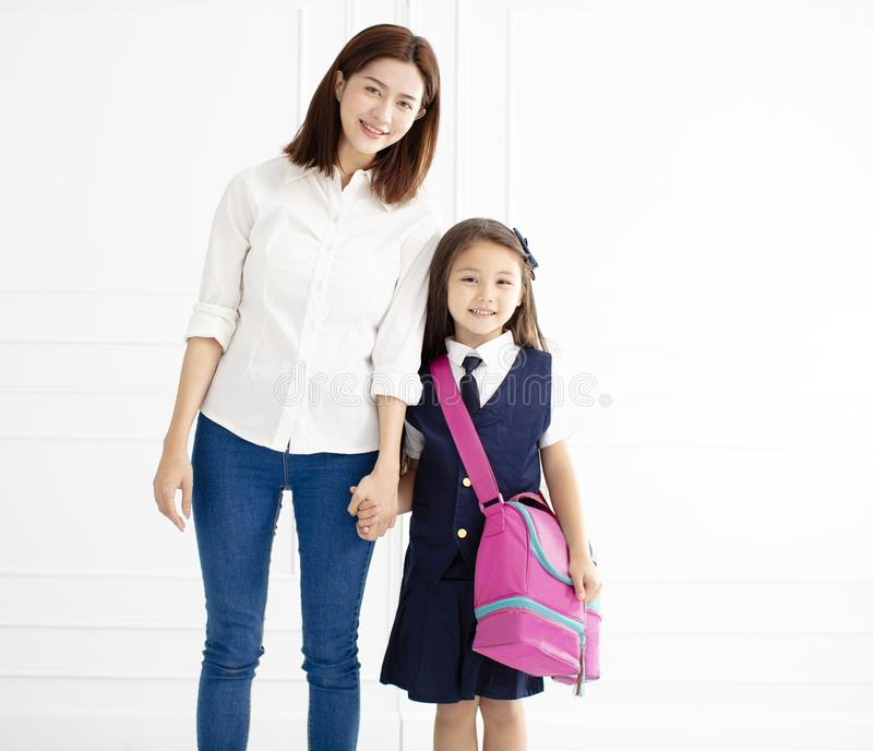 Mother holding hand of daughter ready go to school stock image