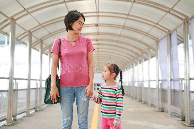Asian mother holding hands her daughter walking on overpass. Mon and child girl walk together.  royalty free stock photos