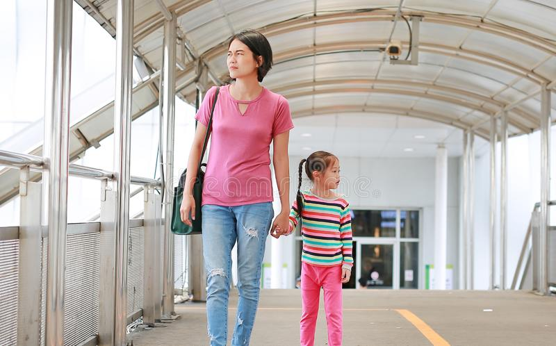 Asian mother holding hands her daughter walking on overpass. Mon and child girl walk together stock photos
