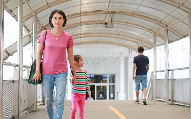 Asian mother holding hands her daughter walking on overpass. Mon and child girl walk together royalty free stock photography