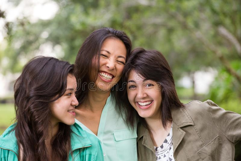 Asian mother laughing and huging her children. stock image