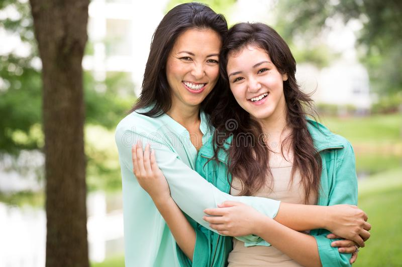 Asian mother laughing and huging her child. royalty free stock photo