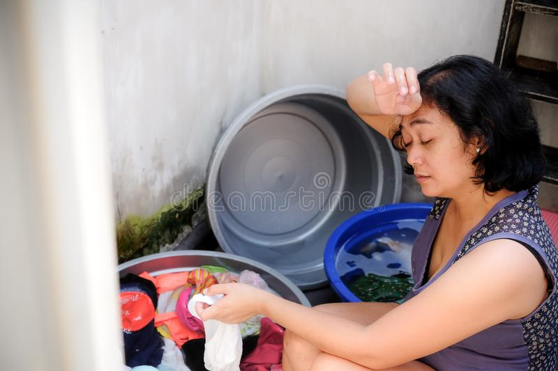 Asian Mother Looking Tired Hand Washing Laundry at Home royalty free stock photography