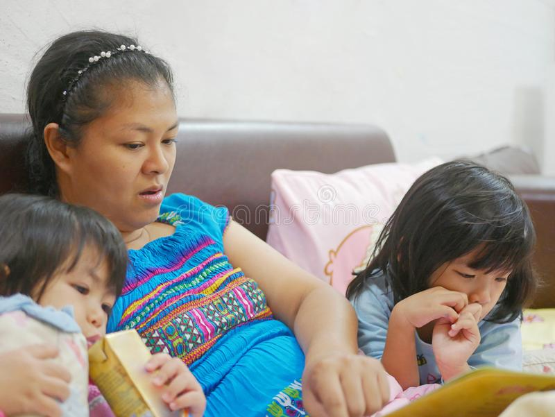 Asian mother opening a story tale book and spending time with her little baby girls, daughters, before their bedtime stock image