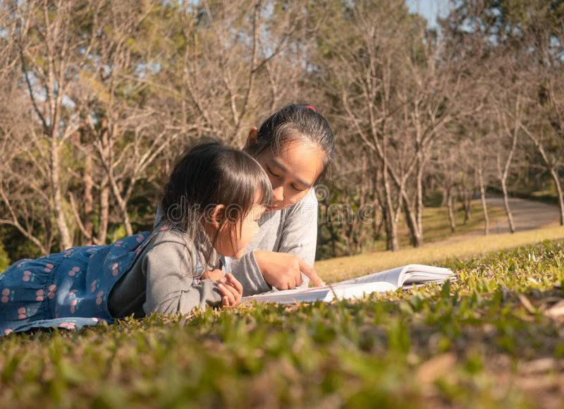 Asian mother reading a book to her daughter in spring garden. Family spending time together on picnic on summer vacation royalty free stock photography
