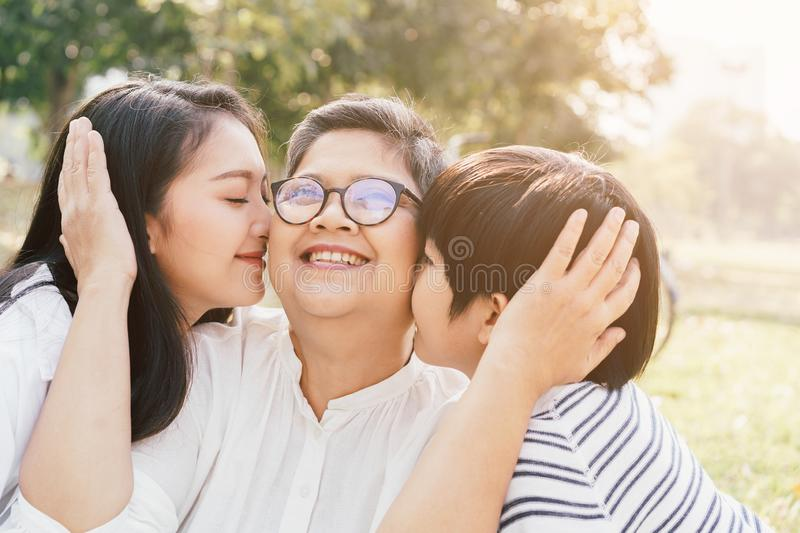 Asian mother and son show love for grandmother by kiss cheeks at the park in the morning. The concept of family lifestyle on the royalty free stock photography