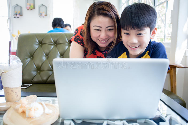 Asian Mother And Son Sitting At Desk Using Laptop At Home stock photography