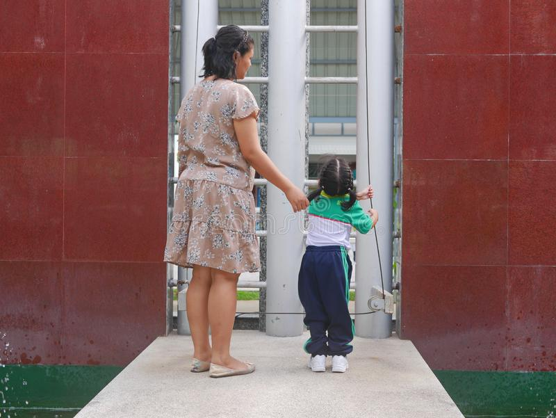 Asian mother standing next to her little daughter while learning to raising a Thai national flag up the school`s flag pole.  royalty free stock image