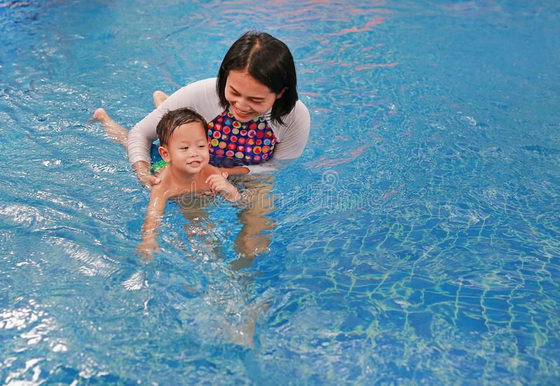 Asian mother take little Asian baby boy in swimming class. Happy toddler enjoying swim in pool with mom stock photography