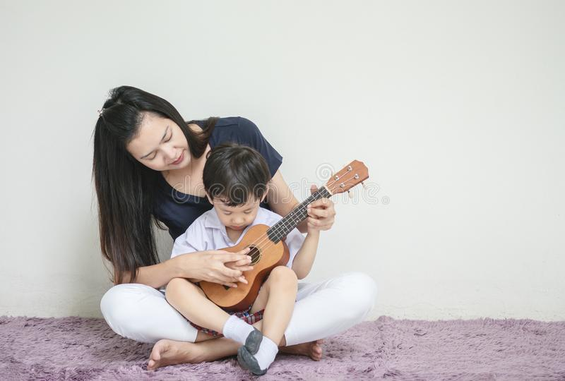 Asian mother teach her son to play ukulele on carpet with copy space royalty free stock photos