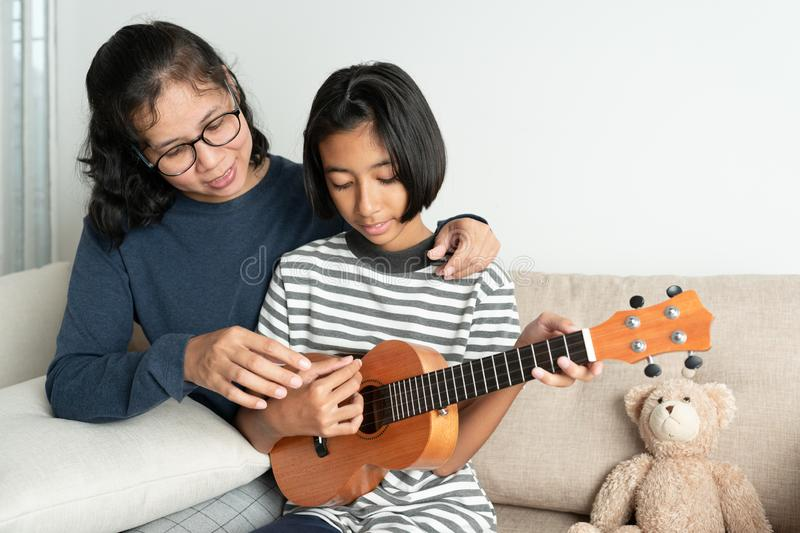 Asian mother teaches her daughter to play ukulele while sitting on the sofa in her home living room royalty free stock image