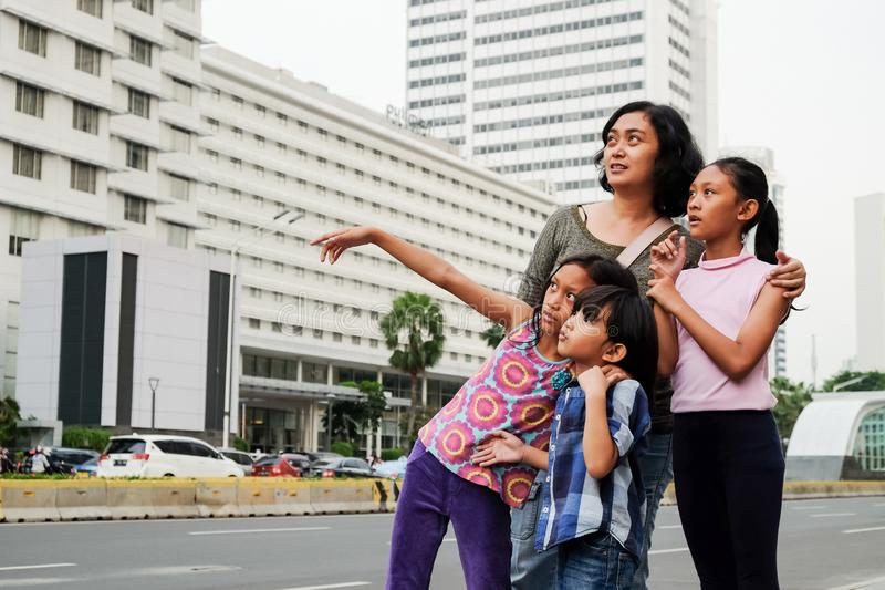 Asian Mother with Three Children Having Fun Walking Around At City Center Looking At City Scene royalty free stock images