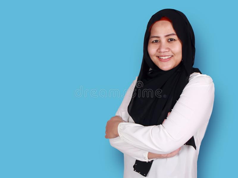 Muslim woman Smiling Friendly. Asian muslim businesswoman wearing hijab smiling friendly with arms crossed, young woman standing over blue background, female stock photography