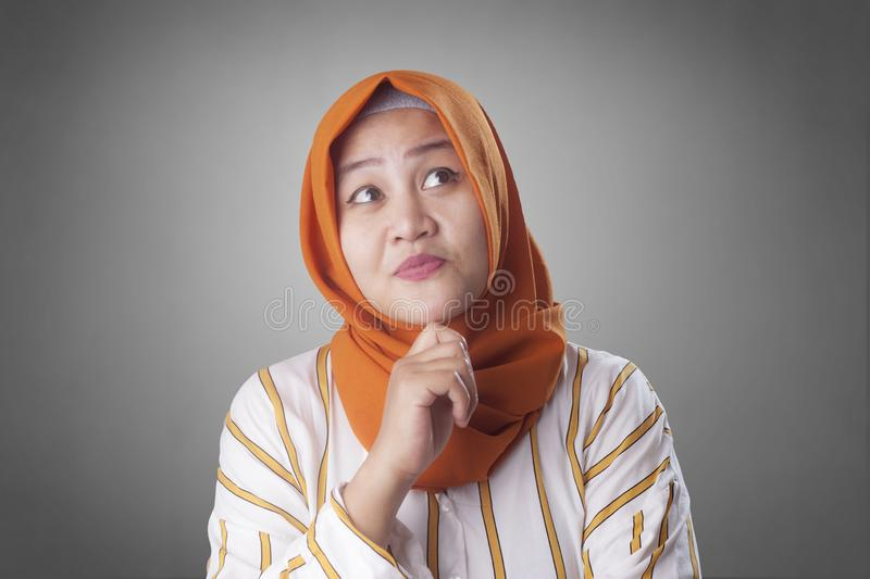 Muslimah Businesswoman Thinking Something, Having Bright Idea. Asian muslim businesswomen wearing hijab with curiousity thinking expression. Having good idea royalty free stock photography