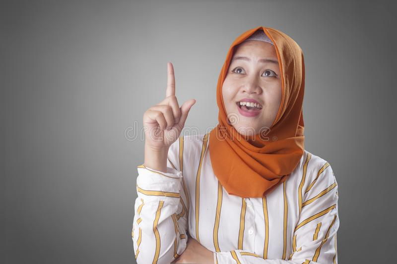 Muslimah Businesswoman Thinking Something, Having Bright Idea. Asian muslim businesswomen wearing hijab with curiousity thinking expression. Having good idea stock images